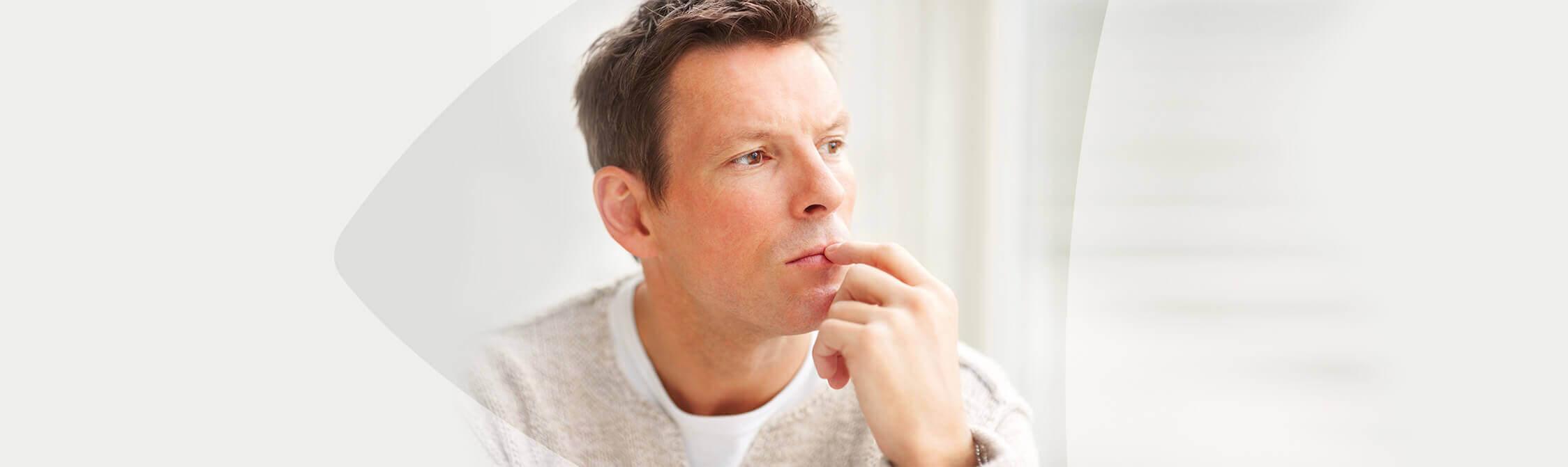 Un homme est assit à une fenêtre, l'air pensif