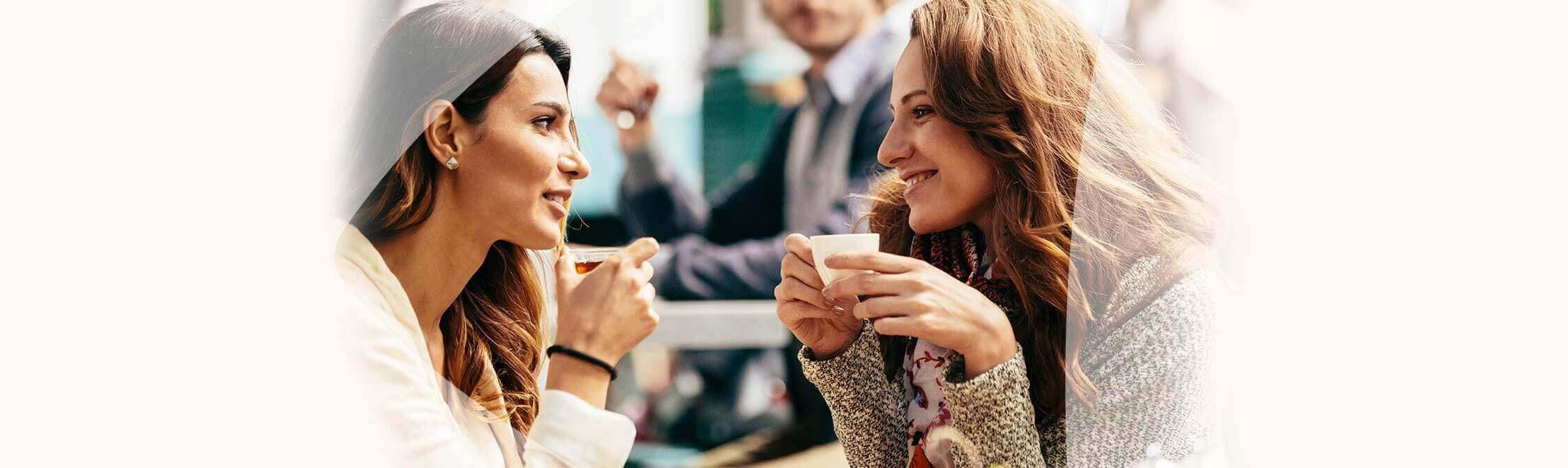 Twee vriendinnen in gesprek op café