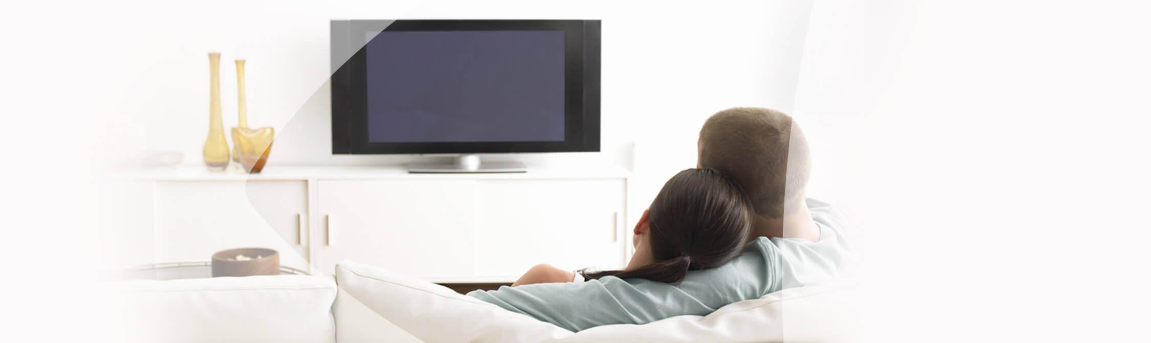 Koppeltje zit op de sofa en kijk tv