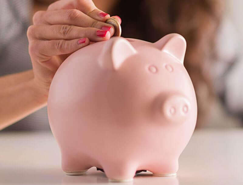 Une femme met des pièces dans un cochon tirelire