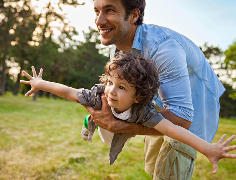 Un homme joue avec un enfant dans la praire