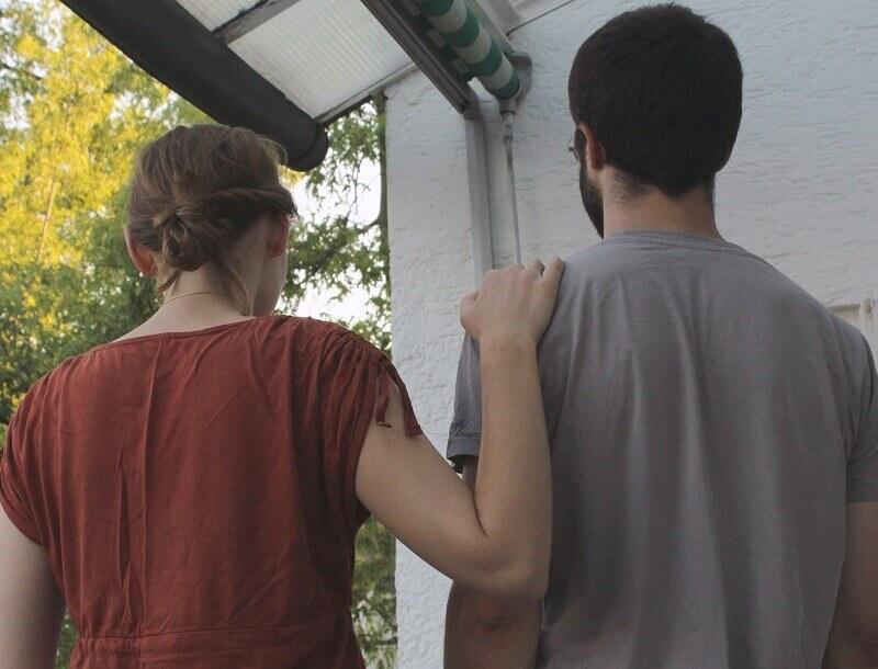 Une femme met sa main sur l'épaule d'un homme