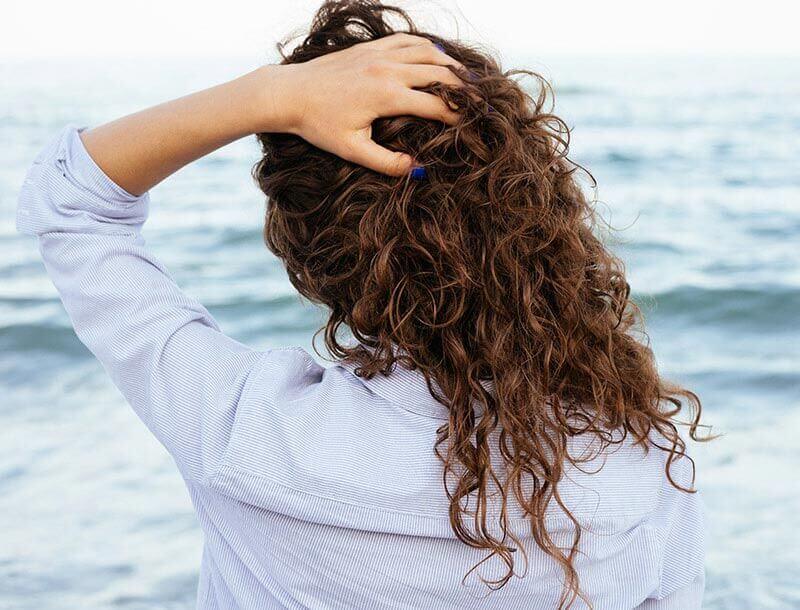 Une femme contemple la mer, les mains dans les cheveux